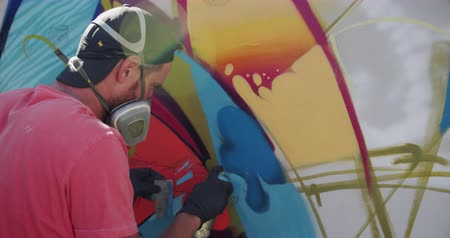 passatempo : Side view of Caucasian graffiti artist painting with aerosol spray on the wall. He is wearing protective mask 4k