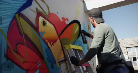 vandalismo : Rear view of Caucasian graffiti artist painting with aerosol spray on the wall. He is using ladder 4k Stock Footage