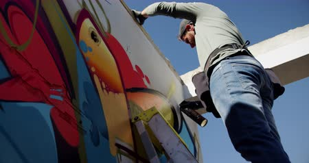čepice : Low angle view of Caucasian graffiti artist painting with aerosol spray on the wall. He is using ladder 4k Dostupné videozáznamy