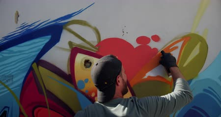 покрытый : Rear view of Caucasian graffiti artist painting with aerosol spray on the wall. He is creative 4k