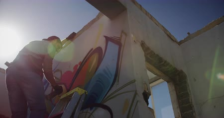 kaplanmış : Low angle view of Caucasian graffiti artist painting with aerosol spray on the wall. He is using ladder 4k Stok Video