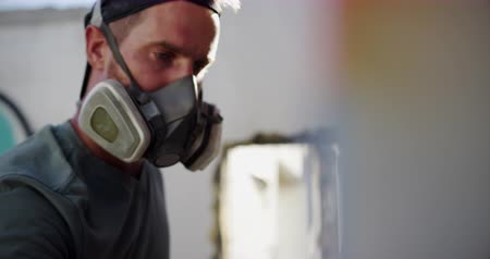 kaplanmış : Side view of Caucasian graffiti artist painting with aerosol spray on the wall. He is wearing protective mask 4k