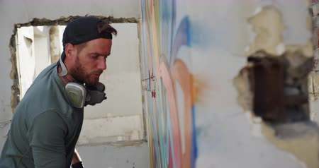spraying : Side view of Caucasian graffiti artist painting with aerosol spray on the wall. He is creative 4k