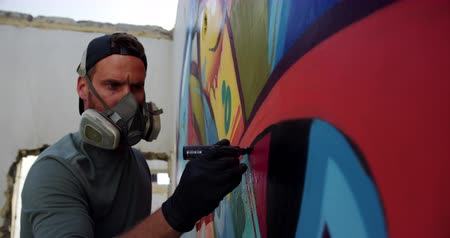 vandalismo : Side view of Caucasian graffiti artist painting with marker on the wall. He is wearing protective mask 4k