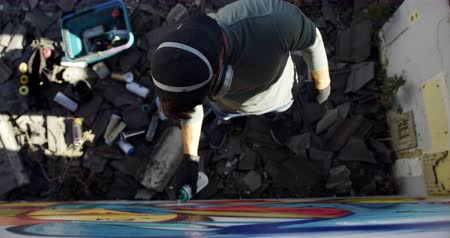 vandalismo : High angle view of Caucasian graffiti artist painting with aerosol spray on the wall. He is wearing protective mask 4k Stock Footage