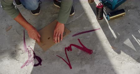 vandalismo : High angle view of Caucasian graffiti artist cutting cardboard with cutter on floor. He is making stencil 4k