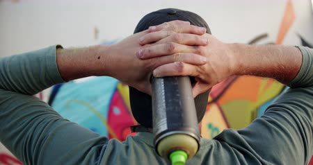 вандализм : Rear view of Caucasian graffiti artist with hands behind head looking at graffiti wall. He is holding aerosol can 4k