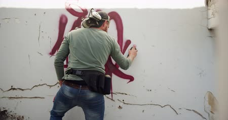 spraying : Rear view of Caucasian graffiti artist painting with aerosol spray on the wall. He is creative 4k