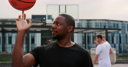 basketball : Front view of African american basketball player playing with basketball in court. He is spinning basketball on a finger 4k Stock Footage