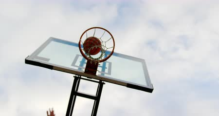 baixo : Low angle view of multi-ethnic basketball players playing basketball in basketball court. They are making a goal 4k