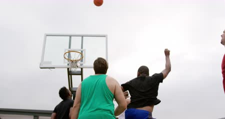 abroncs : Low angle view of multi-ethnic basketball players playing basketball in basketball court. They are making a goal 4k