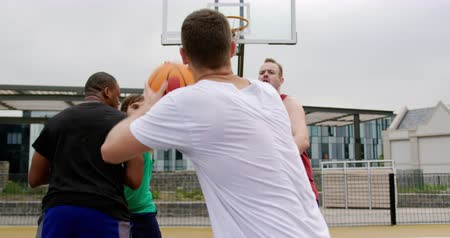 abroncs : Rear view of multi-ethnic basketball players playing basketball in basketball court. Basketball player throwing basketball 4k Stock mozgókép