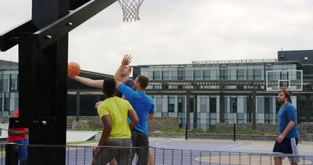 gevangen : Front view of Multi-ethnic basketball players playing basketball in basketball court. They are making a goal 4k Stockvideo