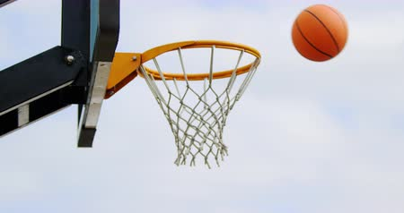outdoor : Basketball going through basketball hoop in basketball court. Close-up of basketball hoop 4k Stock Footage