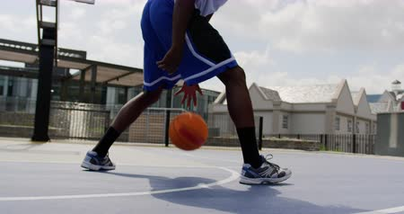 basketball : Low angle view of African american basketball player playing basketball in basketball court. He is dodging basketball 4k Stock Footage