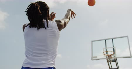 hoop : Low angle view of African american basketball player playing basketball in basketball court. He is throwing ball in basketball hoop 4k Stock Footage
