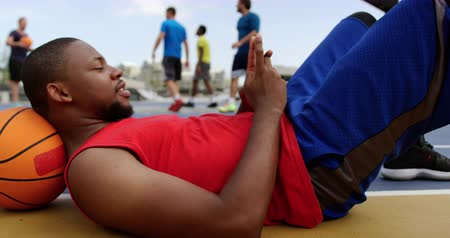 teljes hosszúságú : Side view of African american basketball player using mobile phone in basketball court. He is lying on ground in court 4k