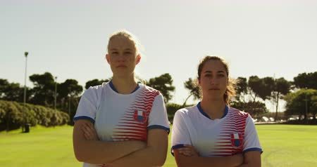 s rukama zkříženýma : Front view of confident Caucasian female soccer players standing with arms crossed at soccer field on sunny day. 4k Dostupné videozáznamy