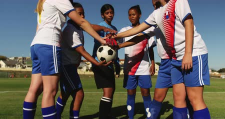 female hands : Front view of happy diverse female soccer team clasping hands together on soccer field on sunny day. 4k