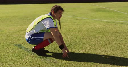 kapitán : Side view of young Caucasian female soccer player explaining strategy while sitting in squat position on soccer field 4k Dostupné videozáznamy