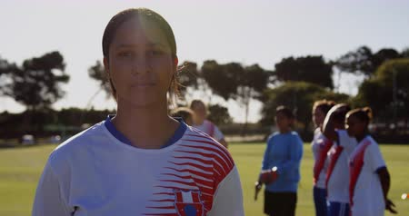 spor ayakkabısı : Portrait of concentrated mixed race female soccer player standing while teammates talk behind her on soccer field on sunny day. 4k