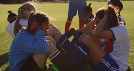 kaptan : Side view of diverse female soccer players doing sit ups exercises on soccer field. 4k