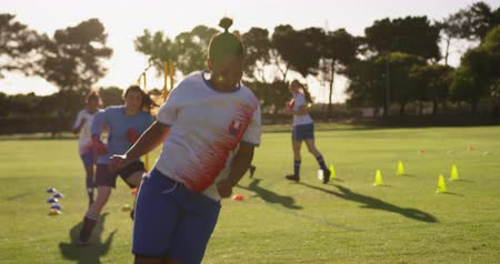 pronto : Front view of diverse female soccer players doing exercises with equipment on soccer field. 4k