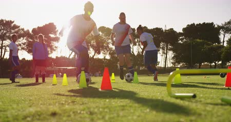 slalom : Front view of diverse female soccer team training with slalom on soccer field 4k