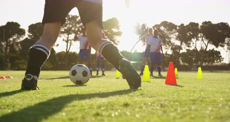 slalom : Side view of diverse female soccer team training with slalom on soccer field 4k