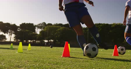 leaping : Front view of diverse female soccer player training with slalom on soccer field 4k