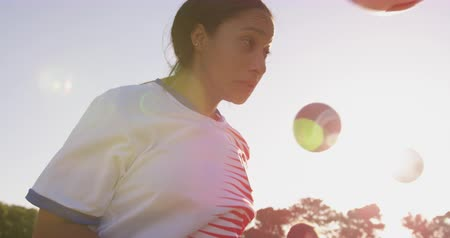 leaping : Side view of mixed race female soccer player shooting the ball with her head on soccer field. 4k