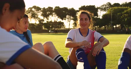 女性 : Front view of diverse female soccer team in break talking to teammates and laughing. 4k