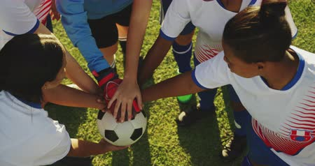 female hands : High angle view of diverse female soccer team clasping hands on soccer field on sunny day. 4k