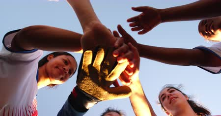 tónusú : Low angle view of diverse female soccer team clasping hands and  smiling cheerfully on soccer field on sunny day. 4k Stock mozgókép