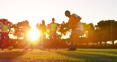 spor ayakkabısı : Side view of African-American soccer player shooting the ball while diverse female soccer team in yellow and orange vests standing on soccer field. 4k
