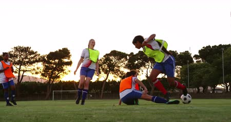keeper : Front view of Caucasian female soccer player tackling down mixed race female soccer player on soccer field. 4k