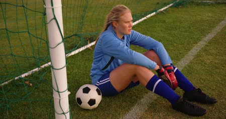 кроссовки : High angle view of Caucasian female soccer player with keeper gloves sitting in the goal on soccer field. 4k Стоковые видеозаписи