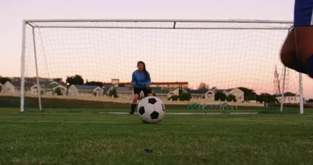 penas : Front view of Caucasian female keeper waiting for female soccer player to shoot the ball on soccer field. 4k