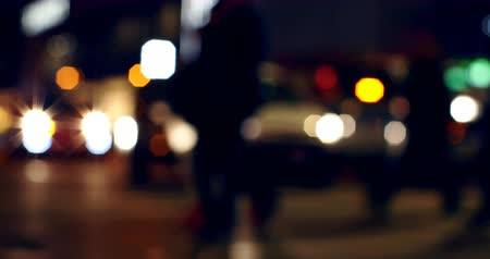 crossing road : Front view of colorful bokeh of car lights at traffic signal on street at night. Pedestrians crossing street 4k Stock Footage