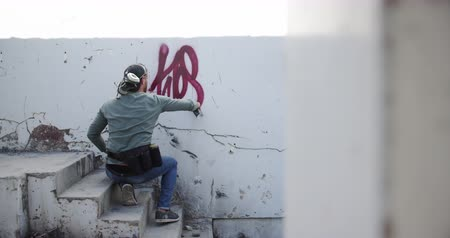 grafiti : Rear view of Caucasian graffiti artist painting with aerosol spray on the wall. He is creative 4k