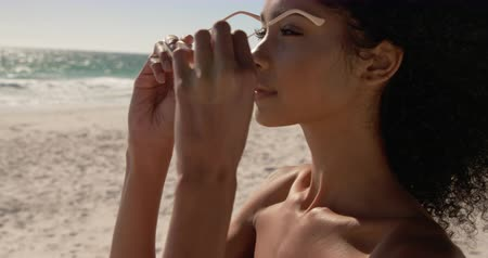 ona : Side view of African american woman wearing sunglasses on the beach. She is looking away 4k
