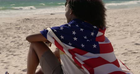 vlastenectví : Side view of African american couple wrapped in American flag sitting together on the beach. They are looking at sea 4k