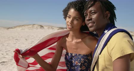 destinace : Side view of African american couple wrapped in American flag sitting together on the beach. They are interacting with each other 4k