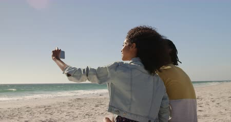 comprimento total : Side view of African american couple taking selfie with mobile phone on the beach. They are having fun 4k
