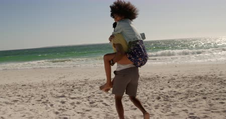 omzunda : Side view of African american man giving piggyback ride to woman on the beach. They are smiling and having fun 4k