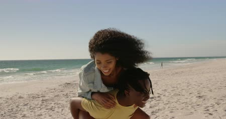 destinace : Side view of African american man giving piggyback ride to woman on the beach. They are smiling and having fun 4k