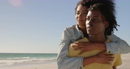 omzunda : Front view of African american man giving piggyback ride to woman on the beach.They are looking away 4k