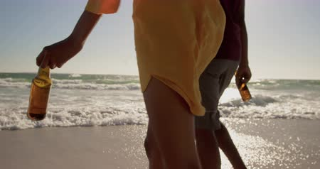 etnia africano : Mid section of African american couple walking together on the beach. They are holding hands 4k