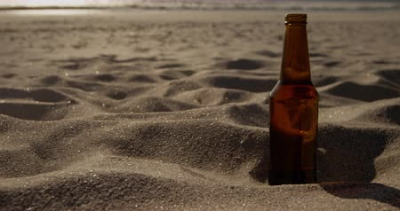 ультра : Front view of beer bottle on sand at beach. Sea waves in the background 4k