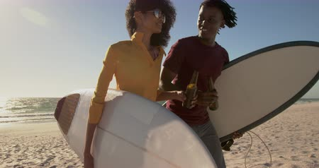 refresco : Side view of African american couple walking together with surfboard on the beach. They are drinking beer 4k
